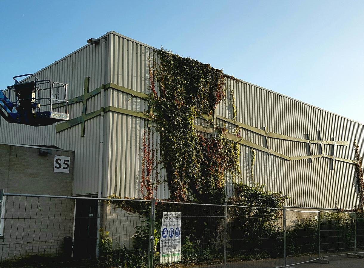 Het kunstwerk van Wim Suermondt wordt vlak voor de sloop van de oude gymzaal van De Werft in Kaatsheuvel gehaald.