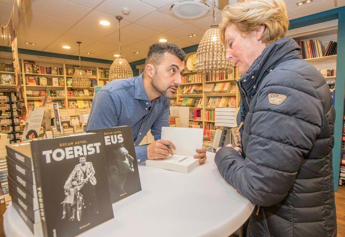 Özcan Akyol signeert bij een boekhandel.