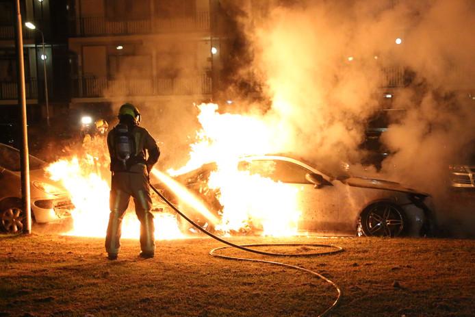 Een hevige autobrand bij de Beethovenlaan in Delft, waar de brandweer de handen vol aan heeft. Vaak staan in brand gestoken voertuigen vlak bij huizen.