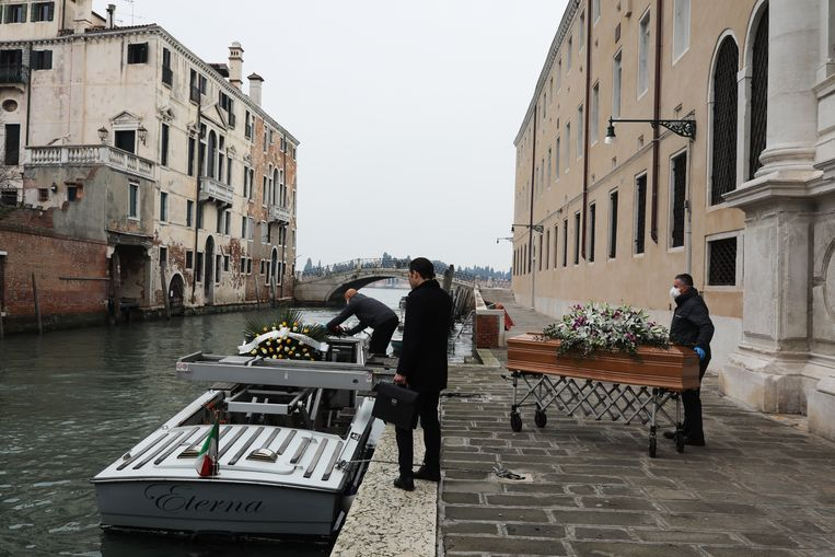 Doodskisten worden vanuit het ziekenhuis in Venetië op een boot geladen. Vanwege het virus gaan veel begrafenissen in Italië niet door. Beeld Getty Images