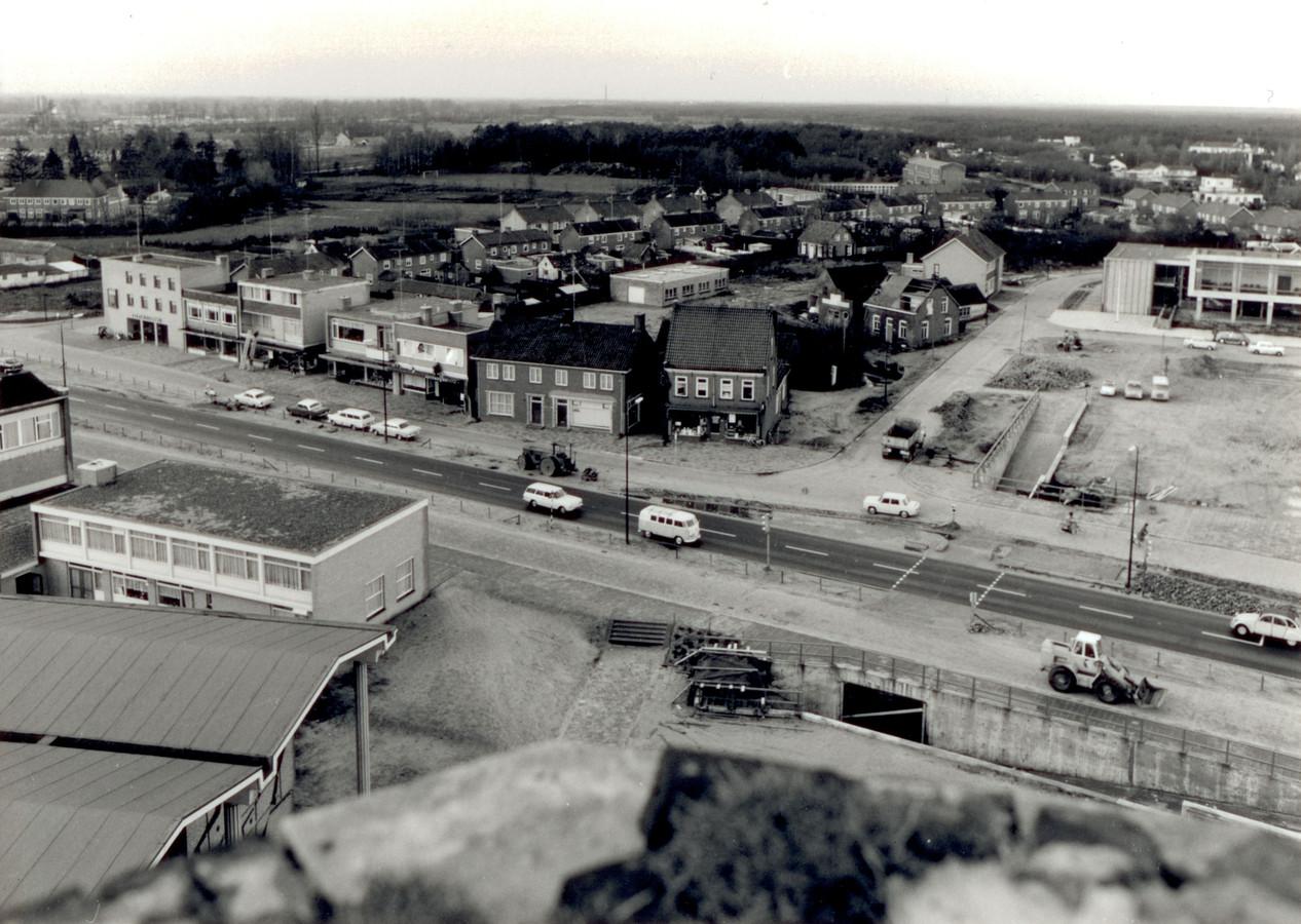 De provinciale weg, met ventwegen, door het centrum van Son in 1965. Rechtsboven het nieuwe gemeentehuis, linksonder de kerk. Archieffoto Heemkundekring Son en Breugel.