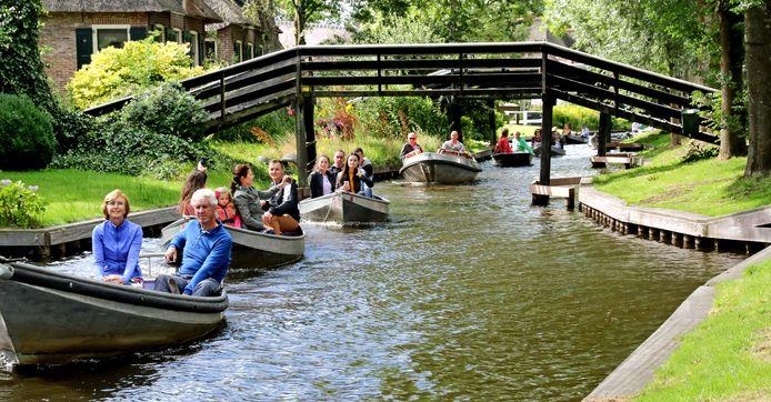 Een optocht van bootjes met toeristen in een van de kanalen van Giethoorn.