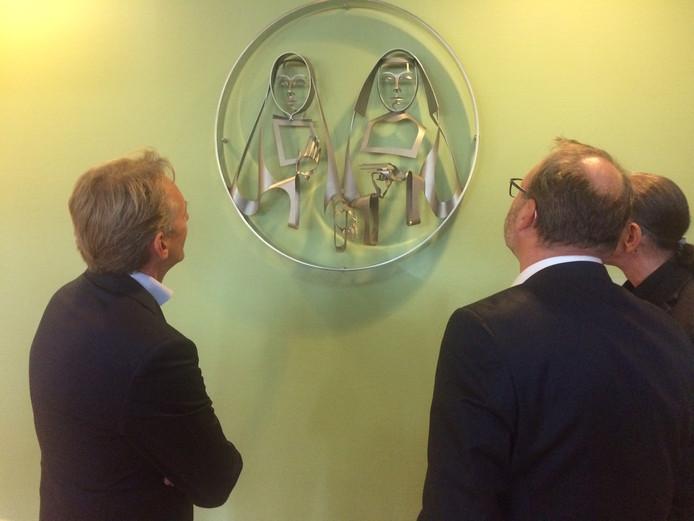 Peter Bennemeer (links) en Geert van den Enden bekijken met de kunstenaar Martien Hendriks (rechts) het nieuwe kunstwerk in de hal van het ziekenhuis.