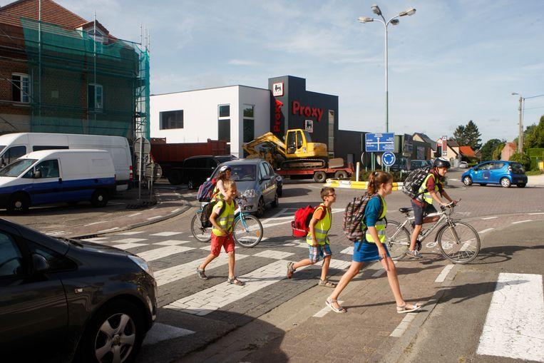 Enkele scholieren steken over aan de rotonde aan de P. Pitetstraat en Prof. Scharpélaan.