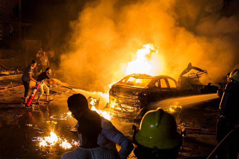 Omstanders proberen brandjes te blussen na de ontploffing bij het oncologisch centrum.