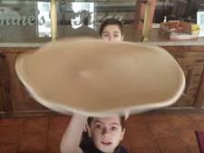 Pizzabakker geeft samen met zoons lesje pizzabodems draaien