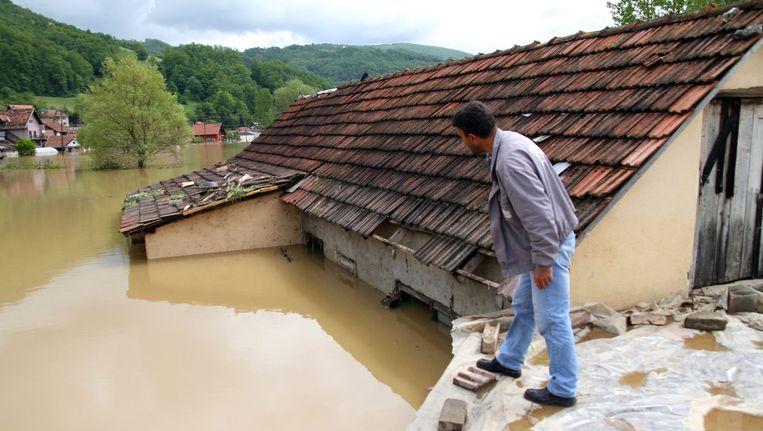 Een bewoner overziet de schade aan zijn huis in Pozega, Servië. Beeld EPA