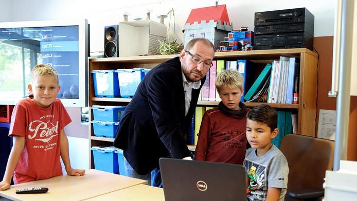 René van Engelen helpt een paar jongens met de voorbereiding van hun presentatie.