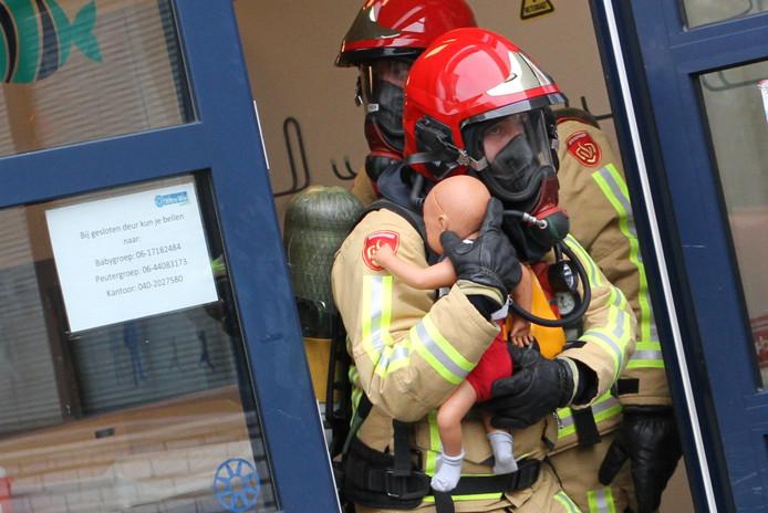 Een brandweerman draagt een 'baby' naar buiten