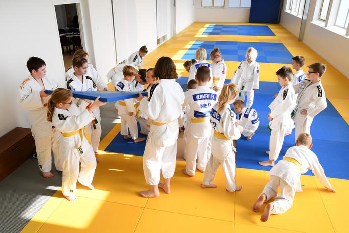 De jeugdige judoka's van Nintai brengen leggen de matten op hun plek in de nieuwe ruimte aan de Meidoornstraat.