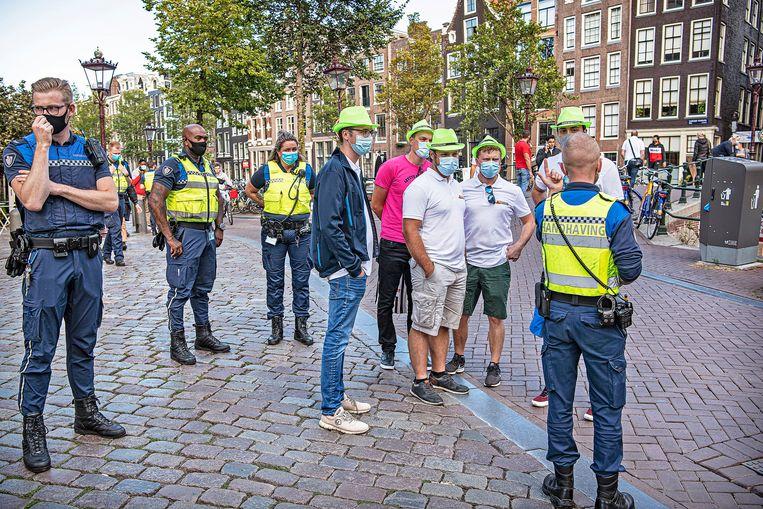 Zondagavond op de Wallen: handhavers hebben zojuist een aantal Duitse toeristen aangesproken omdat ze geen mondkapje droegen. Nu dus wel. Beeld Guus Dubbelman / de Volkskrant