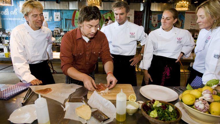 Antonie Kamerling, Jamie Oliver, Paul Rosenmoller en twee gelukkigen krijgen kookles van de beroemde Engelse kok in restaurant Fifteen in Amsterdam. Archieffoto ANP Beeld