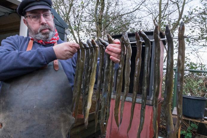 Rinus Smalheer met een spies palingen die klaar zijn om de rookoven in te gaan.