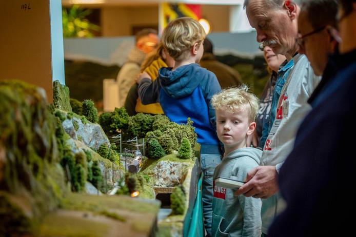 Tentoonstelling van een smalspoormodelbaan naar Zwitsers voorbeeld in Wijchen afgelopen weekend. Felix Pots (8) kijkt aandachtig hoe een lid van de Gennepse vereniging de trein weer laat rijden.
