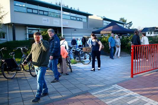 Bezorgde bewoners vertrekken bij een school in Den Dolder na afloop van een gesprek met Minister Sander Dekker van Rechtsbescherming.