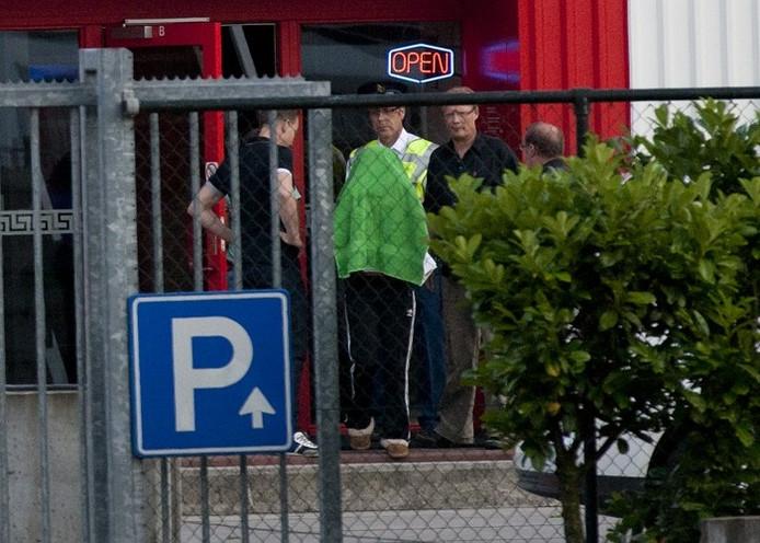 Een getuige van de schietpartij in eroscentrum Escape in Doetinchem wordt onder een handdoek weggeleid. Foto: Theo Kock