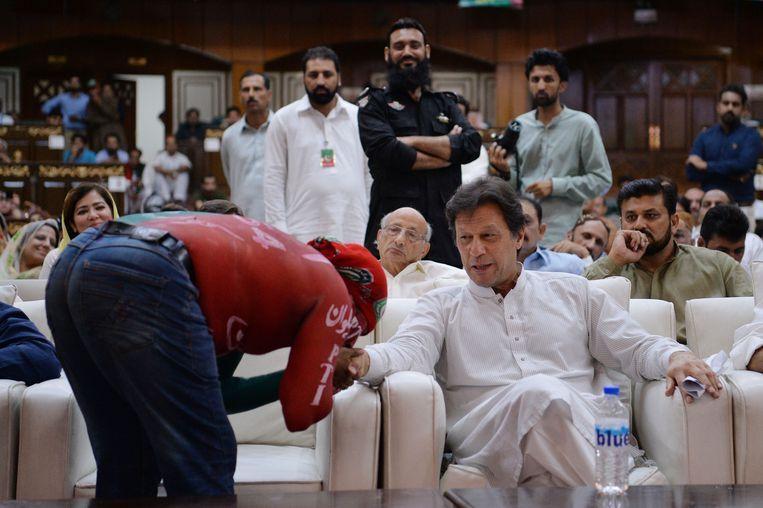 Een aanhanger kust de hand van Imran Khan in Islamabad. Beeld AFP