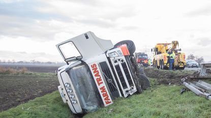 Truck kantelt in gracht na botsing