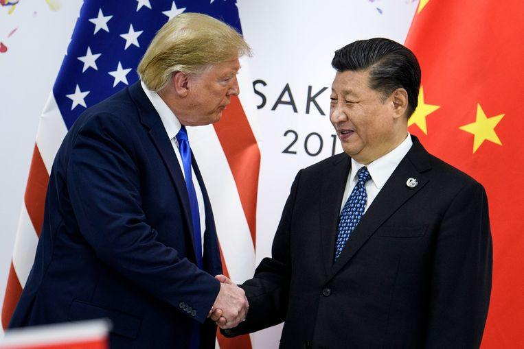 De Amerikaanse president Donald Trump en zijn Chinese ambtsgenoot Xi Jinping schudden elkaar de hand tijdens een ontmoeting op de G20 in het Japanse Osaka in juni van dit jaar. De twee zouden dicht bij een handelsakkoord zijn. Beeld AFP