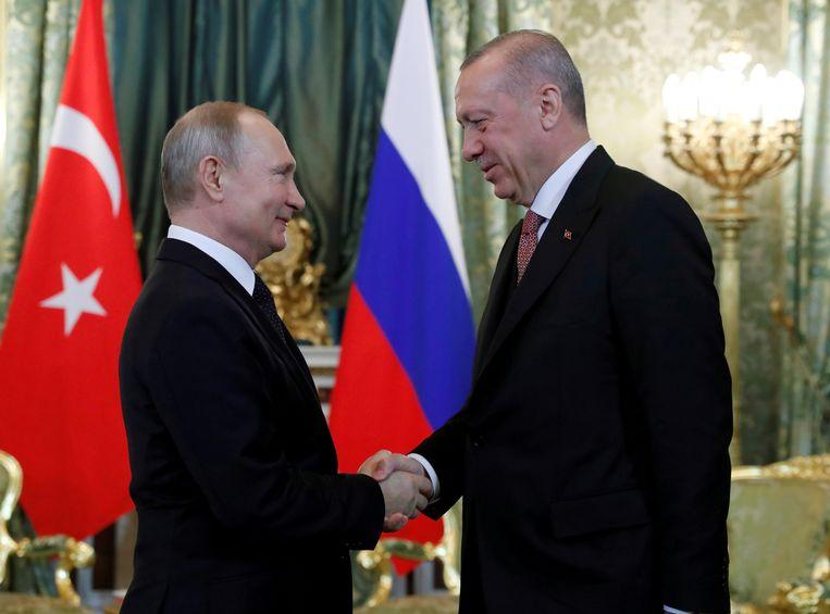 De Russische president Poetin schudt de hand van de Turkse president Erdogan.