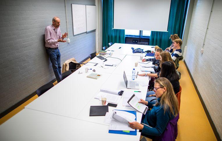 Tweedejaars studenten Nederlands van de Vrije Universiteit in Amsterdam krijgen college van hoogleraar Johan Koppenol.  Beeld Freek van den Bergh / de Volkskrant
