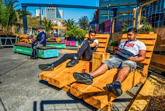 In het nieuwe, tijdelijke 'pocketpark' op de Coolsingel kunnen mensen even uitrusten in de zon.
