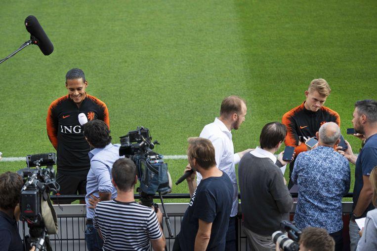 Een lachende Virgil van Dijk staat naast Matthijs De Ligt voor de open training in de aanloop naar de EK-kwalificatiewedstrijd tegen Duitsland.  Beeld ANP