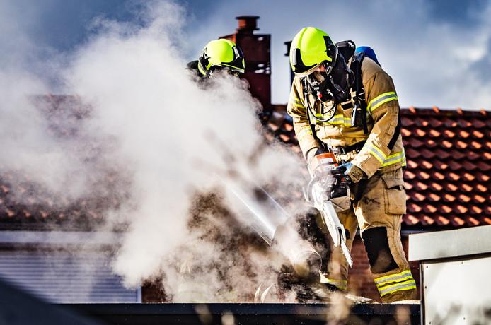 De brandweer moest het dak van een woning open zagen om het vuur te blussen.