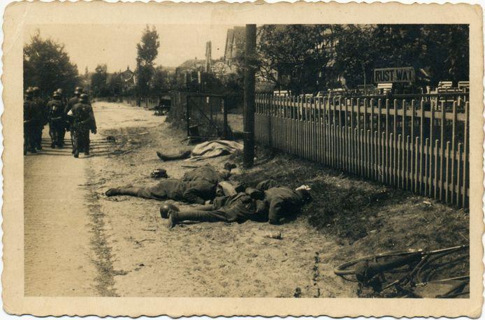 RHENEN, MEI 1940 In de nacht van 10 op 11 mei 1940 begon de Slag om de Grebbeberg. Vanuit Wageningen werd de Duitse artillerieaanval geopend op de voorposten van de Grebbelinie die aan de voet van de Grebbeberg lagen. Hier lag de belangrijkste Nederlandse verdedigingslinie die de toegang tot het westen van het land afschermde. Ondanks de verouderde bewapening boden de Nederlandse militairen echter hevige weerstand. Na twee dagen felle strijd waren de Nederlandse troepen ernstig verzwakt. Op 13 mei moesten zij zich terugtrekken. Tijdens de gevechten aan de Grebbelinie zijn 424 Nederlandse militairen gesneuveld. Op deze foto, genomen bij de Grebbeweg in Rhenen, liggen vier van hen aan de rechterkant van de weg in de berm. In de verte marcheren Duitse militairen verder. Rechts staat het bord van een theeschenkerij en pension met de, in deze context, ironische naam 'Rust Wat'. De gesneuvelde soldaten behoorden zeer waarschijnlijk tot de 8e Compagnie Mortieren.