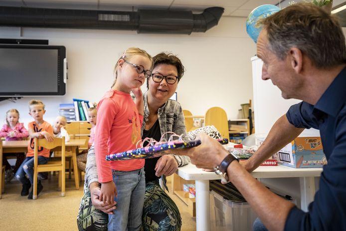 Met dochter Manou bedankt Marieke ten Elsen de directeur George in het Veld en de school met een POP (Passend Onderwijs Pluim).