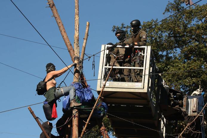 Agenten in een hoogwerker proberen een halfnaakte demonstrante uit een boomhut in het Hambacher bos te krijgen. Het verzet tegen de kap van het bos wordt steeds grimmiger.