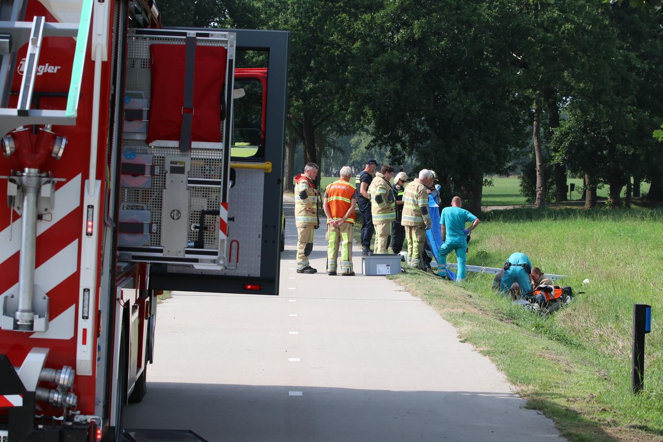 Brandweerlieden ontzetten de van de weg geraakte scootmobieler.
