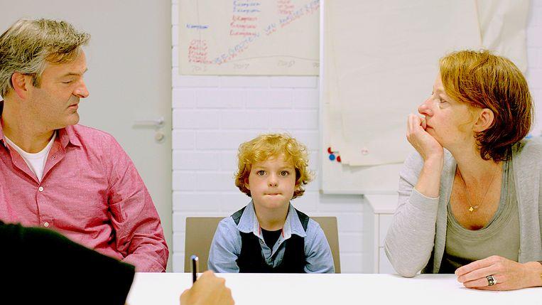 Ouders met hun zoon in overleg met de trainer. Hoeveel uur per week wil hij trainen? Beeld