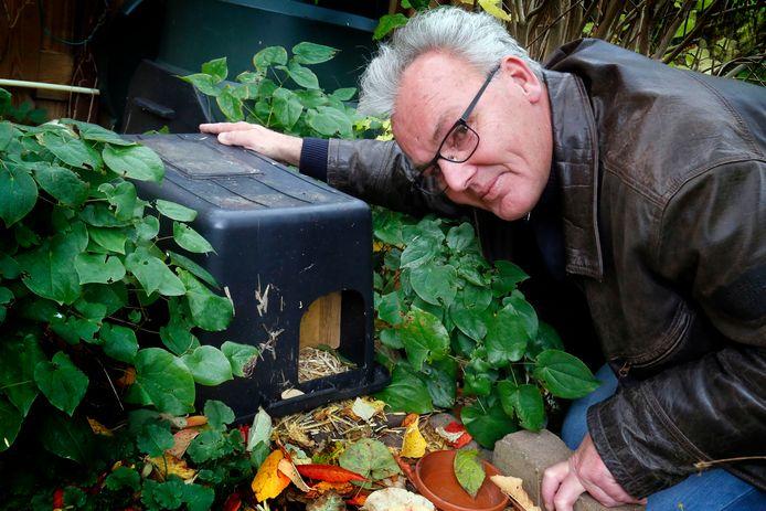 Johan Sterk bij een egelkast in de tuin van Francien Walraven. In zijn eigen tuin is de kast inmiddels zo begroeid dat deze niet zichtbaar meer is.