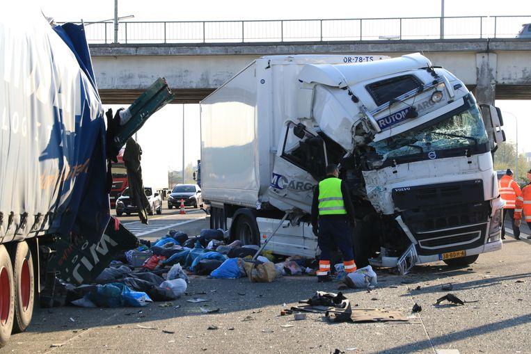 Door de klap scheurde de oplegger van één van de vrachtwagens open en werd de snelweg bezaaid met zakken textiel.