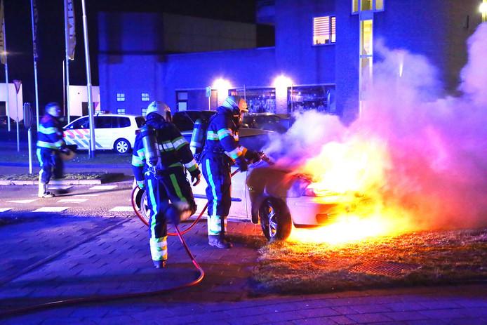 De brandweer poogde de brandende auto te blussen.