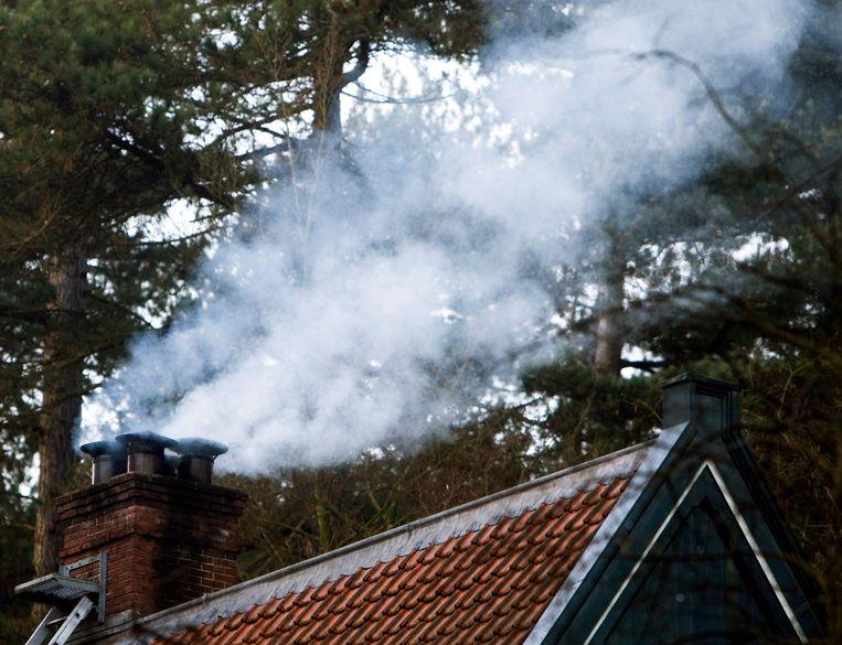 Rook uit de schoorsteen van een huisje in het bos. Beeld ANP XTRA