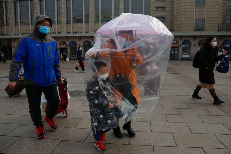 Mondmaskertjes én een plastic hoes om zichzelf en haar zoontje te beschermen: deze moeder aan het station van Peking laat niets aan het toeval over.