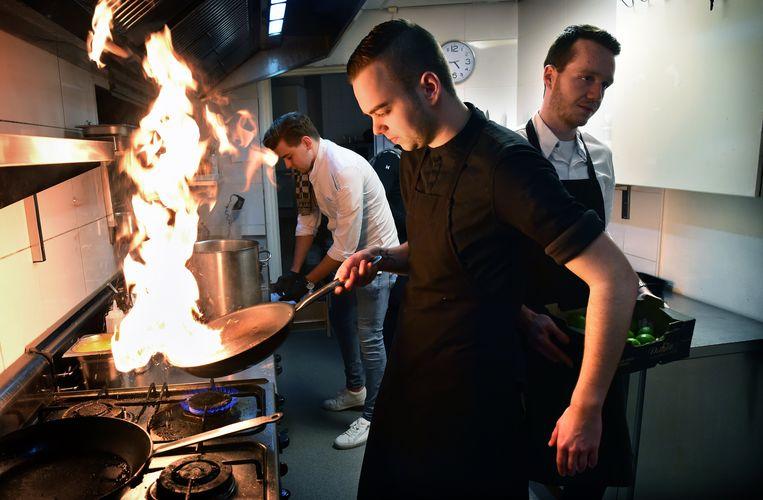 Kok Cas Pikaar aan het werk in zijn keuken van restaurant Doyy. Beeld Marcel van den Bergh / de Volkskrant