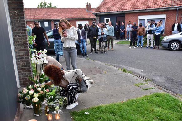 Familie en vrienden houden een ingetogen moment aan het huis in de Mezenstraat. Voor de deur leggen ze bloemen en steken ze kaarsjes aan.