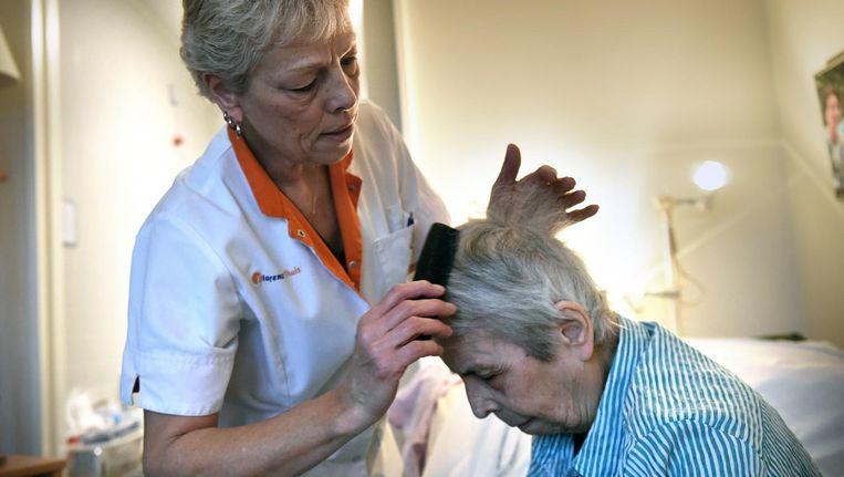 Een verzorger kamt het haar van een bewoner van een verzorgingstehuis Beeld Marcel van den Bergh / de Volkskrant