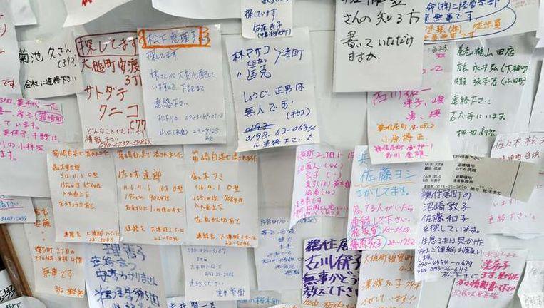 Briefjes van overlevenden, zoekend naar familieleden. Beeld afp