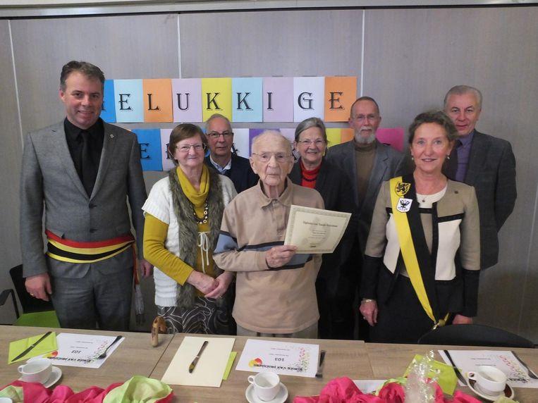 Roger Van Driessche toont fier zijn diploma van oudste Deinzenaar.