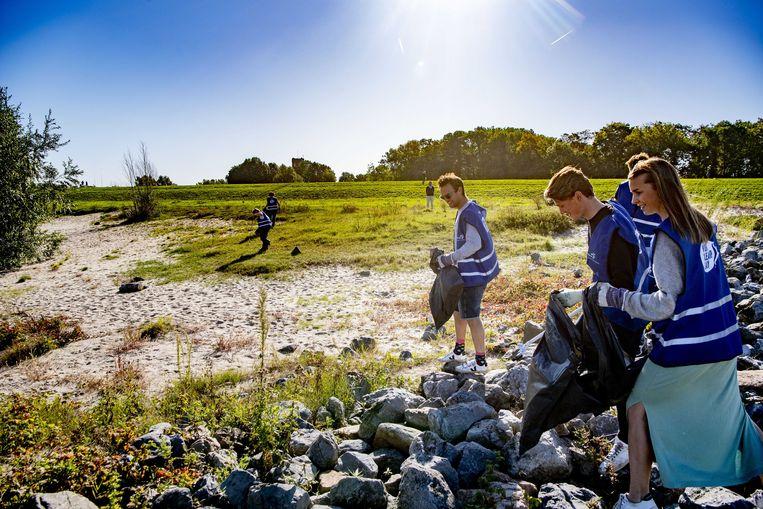 Vrijwilligers ruimen zwerfafval op tijdens World Cleanup Day, een wereldwijde burgeractie om het probleem van zwerfvuil aan te pakken door het organiseren van opruimacties.  Beeld ANP