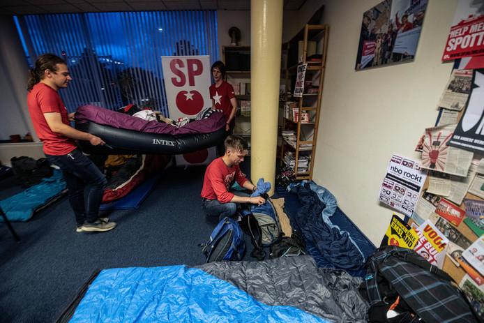 Leden van Rood, de jongerenpartij van de SP en een Duitse student (gehurkt) maken de bedden in orde voor de vijftien studenten die tijdelijk 'op kamers wonen' bij de politieke partij.