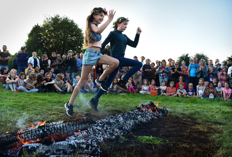 Met een sprong over het Sint Jansvuur, een vreugdevuur, laten de zesdeklassers van de vrije basisschool Tiliander uit Tilburg hun basisschooltijd symbolisch achter zich. Beeld Marcel van den Bergh