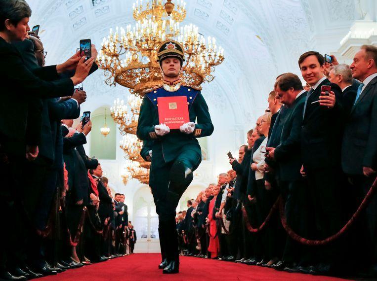 Een lid van de erewacht van het Kremlin draagt de Russische grondwet bij de beëdiging van president Poetin in 2018 voor zijn vierde ambtstermijn. Poetin wil de grondwet nu veranderen, volgens de oppositie om zijn politieke toekomst veilig te stellen. Beeld AFP