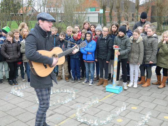 Louis speelt een liedje op zijn gitaar op de speelplaats. De leerlingen hadden met kaarsjes zijn naam gevormd.