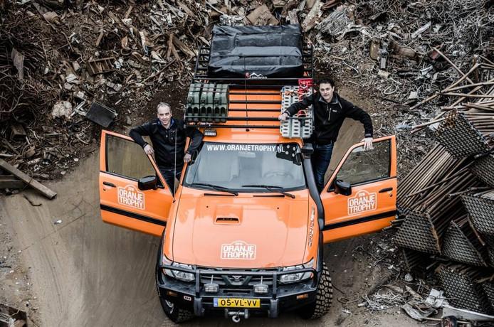 Paul van den Goorbergh en Sander Scherff bij hun oranje bestickerde auto. 'Het wordt daar geen schoolreisje.'