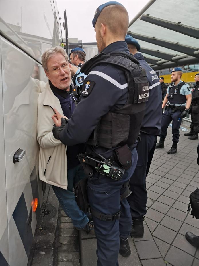 Alfred Blokhuizen wordt door de marechaussee tegen de arrestantenbus gedrukt